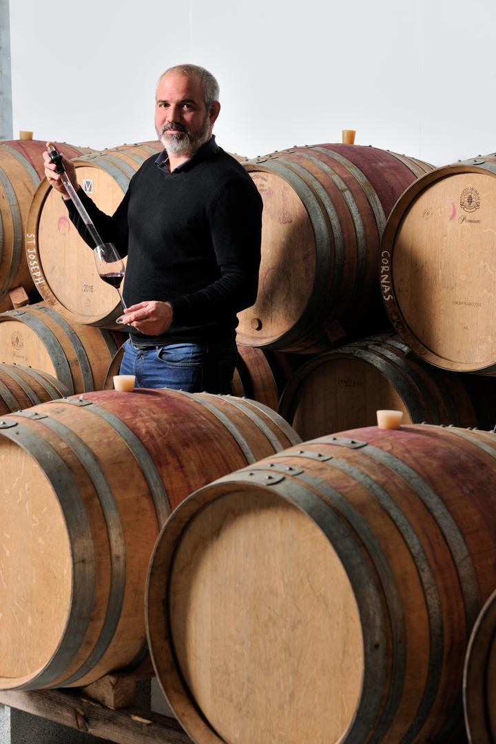 Portrait de Julien Pilon viticulteur dans sa cave devant les tonneaux de vin en bois